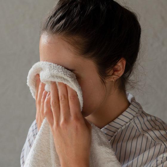 Kvinne tørker ansiktet med håndkle