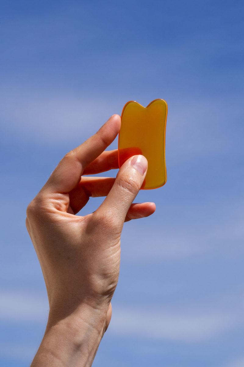 Hånd holder et gua sha-verktøy