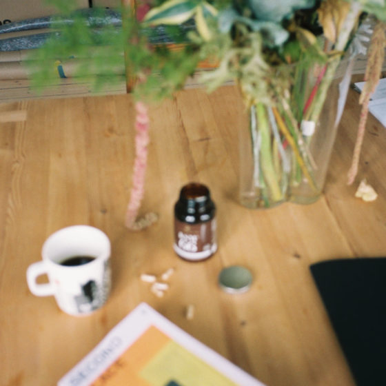 Uskarpt foto av kosttilskudd, bok og kaffekopp